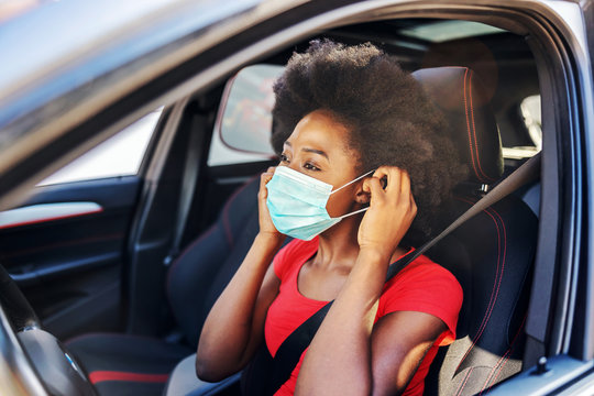Young attractive african woman sitting in her car and putting mask on her face. Covid-19 outbreak concept.