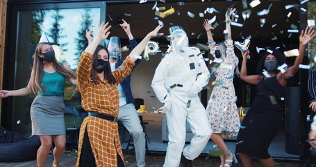 Epic fun party celebration after COVID-19 lockdown. Friends dancing in costumes and masks under confetti slow motion.