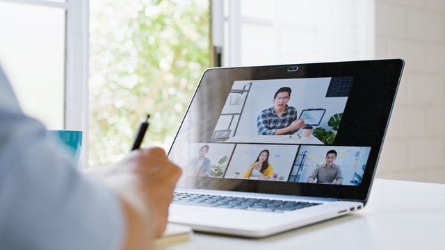 Asian man video call conference, online remote meeting with business coworker, at home. New normal lifestyle, social distancing, internet technology, businessman work from home concept
