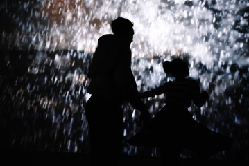 Couple dancing together in dark room with projection of rain drops