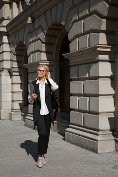Content female office employee in formal wear strolling at city street