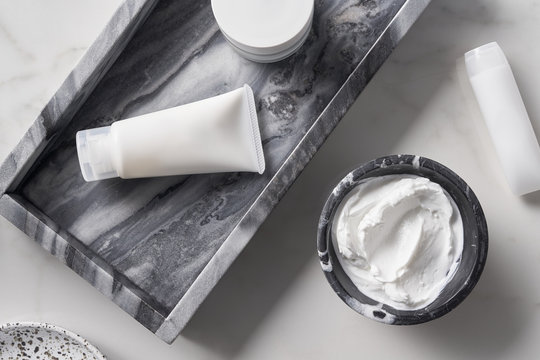 Skincare products near marble tray