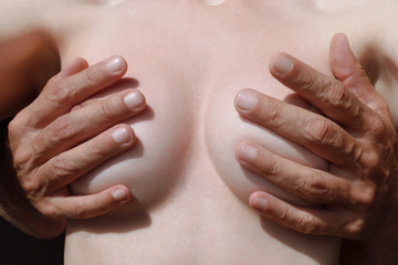 female breasts in male hands closeup