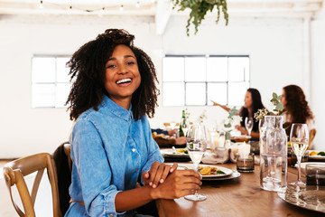 Cheerful black woman with wine during party