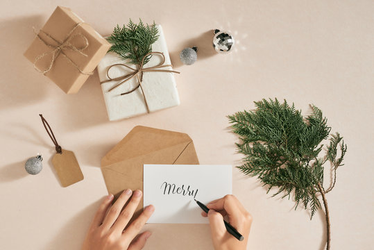 Christmas background with decorations and female hands writing list letter. Flatlay