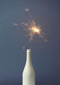 Champagne bottle with sparklers on grey background. Flat lay.