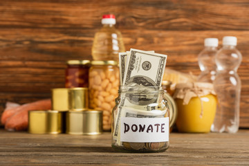 selective focus of jar with money and donated food on wooden background, charity concept
