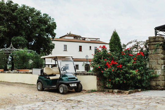 Golf cart parked close to red roses plant in front of country villa