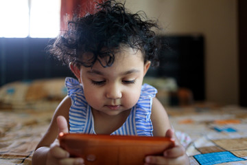 Baby girl watching videos in a mobile phone