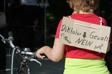 Teilnehmerin an Hygiene-Demonstratoin gegen Corona Einschränkungen mit Plakat