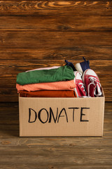 cardboard box with donated clothes and footwear on wooden background, charity concept