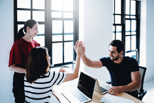 Successful entrepreneurs and business people achieving goals. Happy corporate team giving  high five gesture as they laugh and cheer their succeed, Image motion blur technique