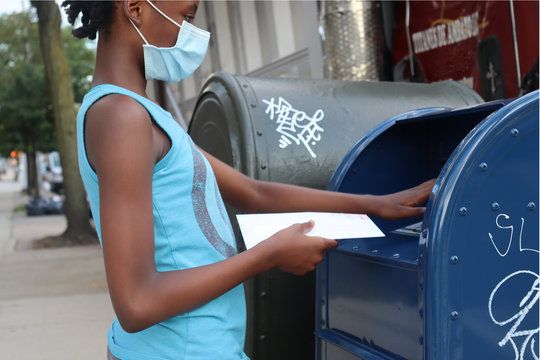 Black Kid with mask on face mailing envelope placing mail in post office box on urban city street