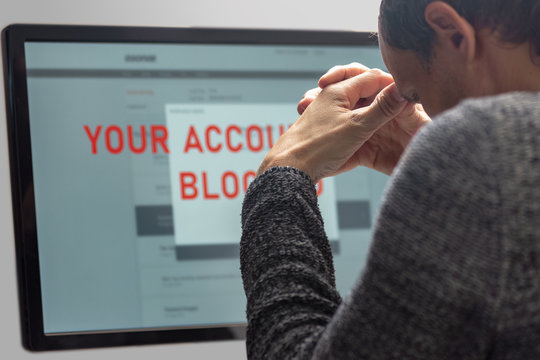 Upset minded man reading text Your account blocked on computer screen