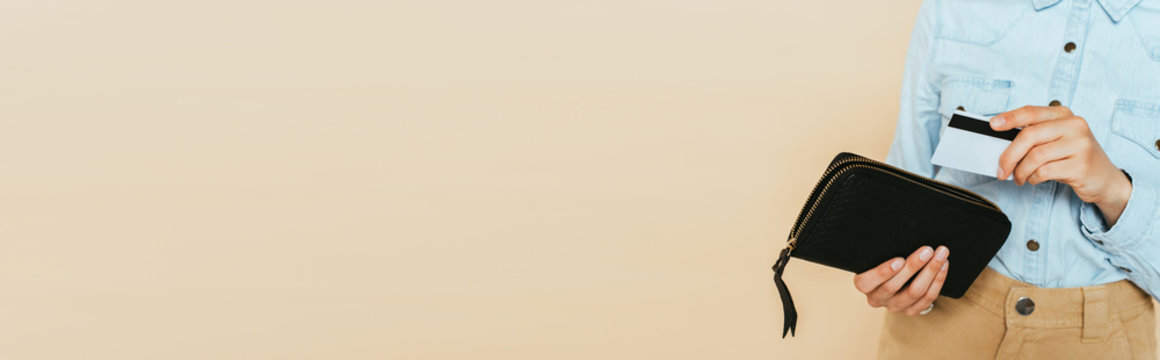 cropped view of woman holding wallet and credit card isolated on beige, panoramic shot