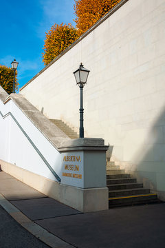 vienna, austria - OCT 17, 2019: back side entrance of albertina museum building. lantern and logo on the stairs. trees in fall foliage. statues on the roof. sunny afternoon