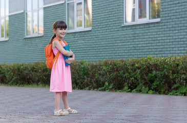 Portrait of little school girl child with backpack and notebooks isolated on a school background
