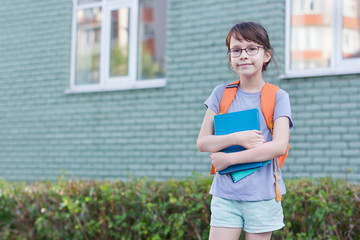 Happy schoolgirl back to school. Portrait of adorable child with backpack and notebook