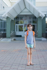Cute happy schoolgirl with backpack leaving school