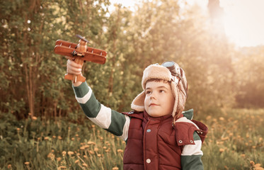 Boy playing in aviator hat with old plane