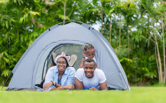 Cheerful african american family enjoying in the park, Mother father and daughter playing camping at outdoor, Happiness family concepts