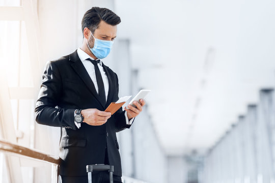 Entrepreneur in face mask using phone while waiting for flight