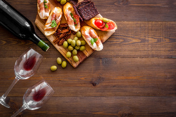 Fototapete - Wine appetizer. Toasts, nuts, olives on wooden desk top view copy space