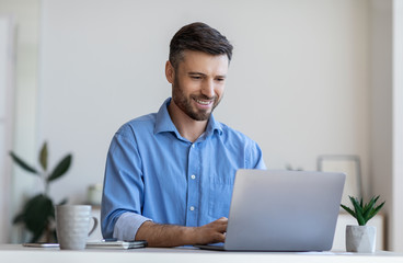 Handsome male entrepreneur working on laptop at desk in modern office