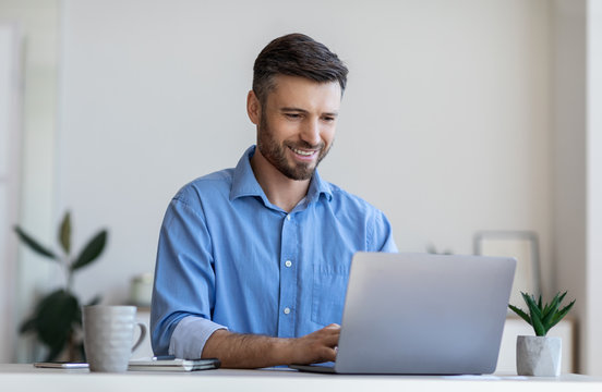 Handsome male entrepreneur working on laptop at desk in modern office