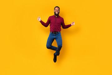 Happy black guy jumping and looking at camera
