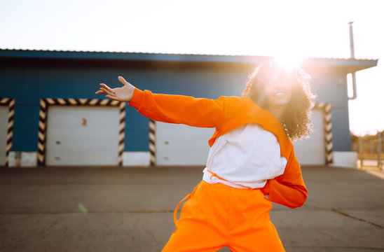 Young African American woman - dancer dancing in the street at sunset. Stylish woman with curly hair in an orange suit  showing some moves. Sport, dancing and urban culture concept.