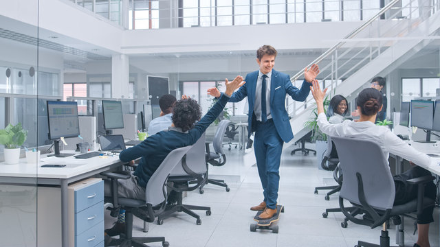 Young Happy Handsome Manager Wearing a Suit and Tie Rides a Longboard. Giving High Fives to Colleagues. Diverse and Motivated Business People Work on Computers in Modern Open Office.