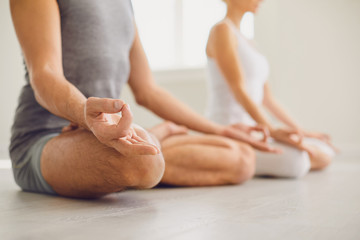 Calm couple meditates relax in lotus position in yoga class.