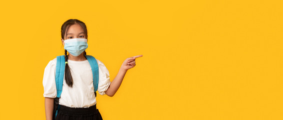 Chinese Schoolgirl Wearing Protective Mask Pointing Finger Aside, Yellow Background