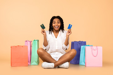 African Woman Holding Credit Cards Sitting Among Bags In Studio