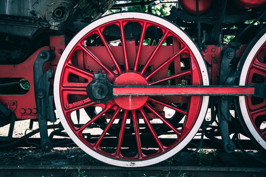 Huge vintage steam locomotive, red painted steel wheel detail close up. Coal-powered steam train stands on a siding. Classic gigantic heavy railway machinery. Side view of power parts of machine.