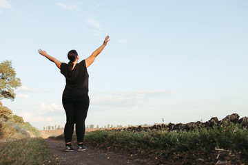 Obraz Body positive, freedom, high self esteem, confidence, happiness, inspiration, success, positive affirmation. Overweight woman celebrating rising hands to the sky - fototapety do salonu