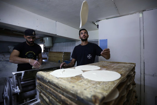Salah Suqi Qasim, who is also a salsa dance teacher,  prepares the dough for baking with his brother at their family bakery in Amman