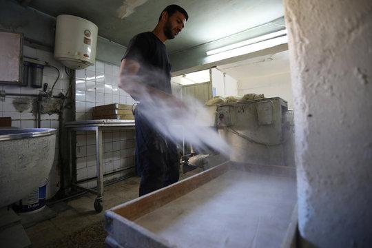 Salah Suqi Qasim, who is also a salsa dance teacher,  prepares the dough for baking at his family's bakery in Amman