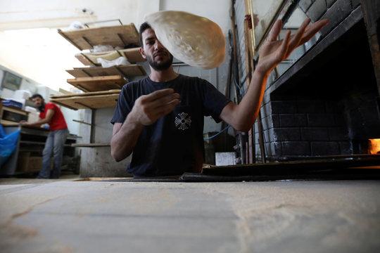 Salah Suqi Qasim, who is also a salsa dance teacher, bakes at his family's bakery in Amman