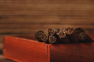 Red wooden box with rolled cigars on wooden table close up