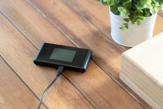 Pocket wifi with battery charger on brown wood table