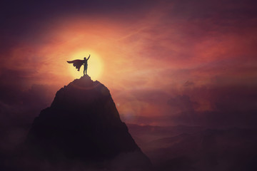 Conceptual sunset scene, superhero with cape standing brave on top of a mountain looks determined at horizon raising one hand up as a winning leader. Hero power and motivation, overcoming obstacles. Fotomurales