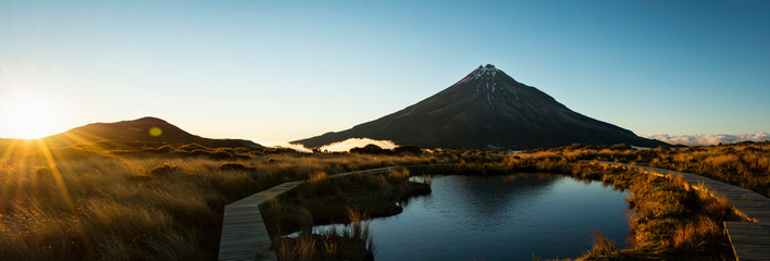 Panoramic image of Mt Taranaki reflected in Pouakai tarn at sunrise, New Zealand
