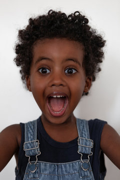 three year old black boy with curly hair in white background