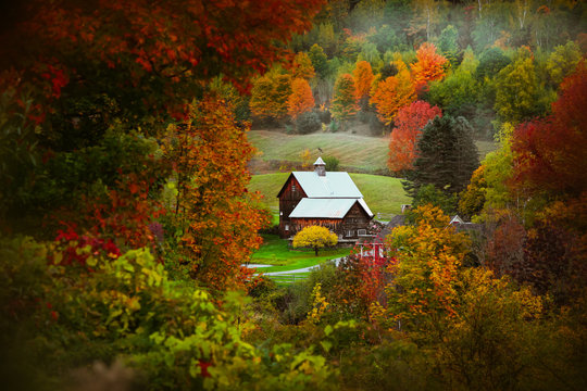 Barn in rural Vermont nestled between fall foliage