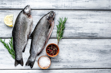 Raw trout fish with spices and ingredients on wooden background with copy space for your text