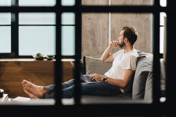 Matur man sitting on couch with laptop on lap, looking away, thinking
