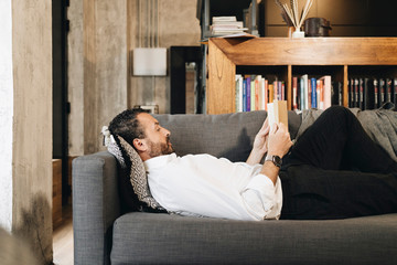 Mature man lying on couch, relaxing, reading book