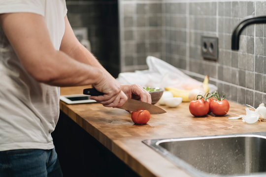 Mature man standing in kitchen, slicing tomatoes